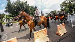 Anggota polisi berkuda berjaga di depan Istana Merdeka, Jakarta, Kamis (12/1). Aksi tersebut tidak hanya digelar di Jakarta, tetapi serentak di 18 kota lainnya di seluruh Indonesia. (Liputan6.com/Faizal Fanani)