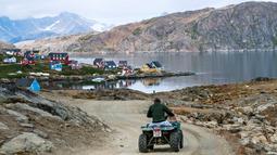 Seorang warga mengendarai ATV di Desa Kulusuk, Kota Sermersooq, Greenland, Denmark, 19 Agustus 2019. Desa Kulusuk ditinggali sekitar 280 orang. (Jonathan NACKSTRAND/AFP)