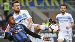 Bek Lazio, Francesco Acerbi, berebut bola dengan striker Inter Milan, Keita Balde, pada laga Serie A di Stadion Giuseppe Meazza, Minggu (31/3). Inter Milan takluk 0-1 dari Lazio. (AP/Antonio Calanni)