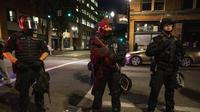 Penjagaan ketat oleh petugas kepolisian pada Sabtu 29 Agustus 2020 usai terjadinya penembakan dalam aksi protes yang meledak di Portland. (AP/ Paula Bronstein)