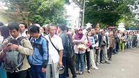 Pelamar calon pegawai negeri sipil (CPNS) Kota Sukabumi mengantri untuk mengambil kartu ujian seleksi di Gedung Juang, Sukabumi, Jawa Barat. (Antara)