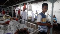 Pasien dievakuasi keluar rumah sakit di Bali menyusul gempa Lombok, Senin (6/8). Gempa 7 pada skala richter yang berpusat di Lombok, menyebabkan kerusakan bangunan di berbagai lokasi di Bali dan mengakibatkan sejumlah warga terluka. (AP/Firdia Lisnawati)