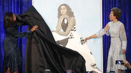 Istri Presiden AS ke-44 Barack Obama, Michelle Obama menarik kain saat upacara peresmian di Galeri Potret Nasional Smithsonian, Washington DC (12/2). Sedangkan lukisan potret Michelle Obama dibuat oleh Amy Sherald. (Mark Wilson/Getty Images/AFP)