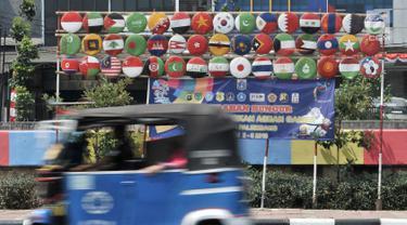 Bajaj melintas di depan instalasi berupa bendera negara-negara peserta Asian Games 2018 di Jalan Tanah Tinggi Barat, Kelurahan Bungur, Kecamatan Senen, Jakarta, Minggu (15/7). (Merdeka.com/Iqbal S. Nugroho)