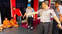 Dua tersangka perampasan HP dan pemaksa muda-mudi buat cabul di Mapolda Riau. (Liputan6.com/M Syukur)