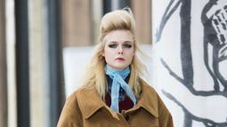 Aktris Elle Fanning memperagakan busana karya Miu Miu pada Paris Fashion Week Fall-Winter 2018, Selasa (6/3). Rambutnya ditata dengan style sasak tinggi seperti mode rambut tahun 60an dan polesan make up smooky eyes yang bold (Vianney Le Caer/Invision/AP)