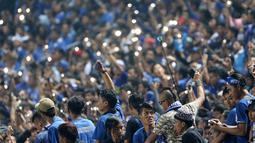 Aksi Bobotoh menyalakan lampu saat mendukung timnya melawan Persija Jakarta pada Torabika SC 2016 di Stadion Gelora Bandung Lauta Api, Bandung, Sabtu (16/7/2016). (Bola.com/Nicklas Hanoatubun)