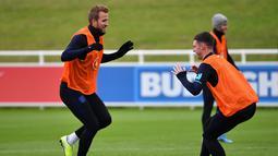 Striker Inggris Harry Kane (kiri) dan bek  Declan Rice (kanan) melakukan pemanasan saat mengikuti sesi latihan tim di St George's Park di Burton-on-Trent (6/9/2019). Inggris akan bertanding melawan Bulgaria pada grup A kualifikasi Euro 2020 di stadion Wambley. (AFP Photo/Paul Ellis)