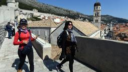 Wisatawan berjalan di atas benteng kota tua Dubrovnik pada 28 Maret 2019. Tahun lalu lebih dari 1,2 juta turis mengunjungi Dubrovnik, kota yang paling banyak dikunjungi di Kroasia. (Denis LOVROVIC / AFP)