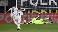Pemain Real Madrid Karim Benzema (kiri) mencetak gol lewat tendangan penalti ke gawang Cadiz yang dijaga kiper Jeremias Ledesma pada pertandingan La Liga Spanyol di Stadion Ramon Carranza, Cadiz, Spanyol, Rabu  (21/4/2021). Real Madrid menang 3-0. (AP Photo/Jose Breton)