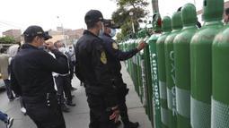 Polisi menandai tangki oksigen kosong dengan nomor berdasarkan kedatangan saat membantu menjaga ketertiban di luar toko isi ulang, Callao, Peru, Senin (25/1/2021). Di tengah pandemi COVID-19, beberapa orang mengatakan mereka telah antre sehari sebelumnya. (AP Photo/Martin Mejia)