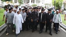 Presiden Joko Widodo  berjalan bersama para kiai dan habib se-Jadetabek  di Istana Negara, Jakarta, Kamis (7/2). Para kiai dan habib berharap Jokowi dapat melanjutkan pembangunan Indonesia. (Liputan6.com/Angga Yuniar)