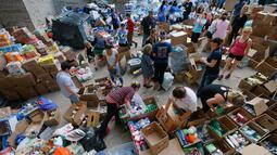 Para relawan mengatur bermacam barang hasil penggalangan dana untuk korban Harvey di Dallas Utara, Selasa (29/8). Para donatur bisa memberikan bantuan berupa barang atau uang melalui situs milik Charity Navigator. (Tony Gutierrez/AP)