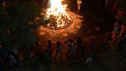 Warga melakukan ritual api unggun Holika di Ahmedabad, India, Minggu (12/3). Umat Hindu setempat menyalakan api unggun Holika pada malam sebelum festival Holi. (AFP PHOTO / SAM PANTHAKY)