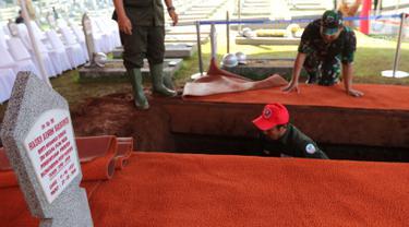 Pekerja menggali makam Presiden ke-3 RI BJ Habibie di TMP Kalibata, Jakarta, Kamis (12/9/2019). Makam Habibie bersebelahan dengan sang istri tercinta, Ainun Habibie. (Liputan6.com/Herman Zakharia)