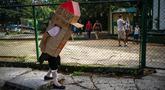 "Feridia Rojas, seorang pensiunan perawat, memakai kotak kardus untuk melindungi dirinya dari penyebaran virus corona Covid-19 di Havana, Kuba, 8 Juli 2020. Kardus pelindung pensiunan berusia 82 tahun itu dilengkapi pesan yang ditulis tangan ""I'm home, and you?."" (AP Photo/Ramon Espinosa)"