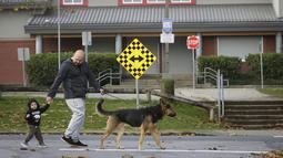 Warga berjalan melewati Sekolah Dasar Cambridge yang ditutup karena wabah COVID-19 di Surrey, British Columbia, Kanada (15/11/2020). Kanada melaporkan total 295.074 kasus dan 10.947 kematian hingga Minggu (15/11) sore waktu setempat, menurut CTV. (Xinhua/Liang Sen)