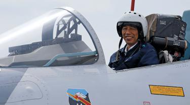 Presiden Jokowi saat berada di kokpit jet tempur Sukhoi Su-27/30 di Natuna, Kepulauan Riau, Kamis (6/10). Tak hanya meninjau kekuatannya saja, Jokowi juga melihat langsung aksi alutsista milik TNI. (REUTERS/Beawiharta)