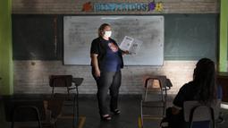 Luz Aranda mengajar kelas bahasa Guarani sekolah tujuh pada hari pertama kelas tatap muka di National School 1044 Santa Ana, Asuncion, Paraguay, Senin (30/8/2021). Sekolah tatap muka digelar setelah satu setengah tahun belajar jarak jauh di tengah pandemi COVID-19. (AP Photo/Jorge Saenz)