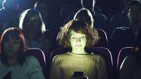 Ilustrasi main ponsel di bioskop