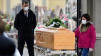 Seorang gadis menyentuh peti mati kerabat yang meninggal saat upacara pemakaman selama masa lockdown untuk menghentikan penyebaran pandemi virus corona COVID-19 di pintu masuk kuburan kecil Bolgare, Lombardy, Italia, Senin (23/3/2020). (Piero CRUCIATTI / AFP)