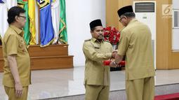 Pelaksana Tugas Gubernur Aceh, Nova Iriansyah menyerahkan surat penugasan Pelaksana Tugas (Plt) Bupati kepada Wakil Bupati Bener Meriah Tgk. H. Sarkawi di Kemendagri Jakarta, Senin (9/7). (Liputan6.com/Herman Zakharia)