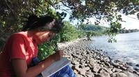 Marcella dengan tekun mengikuti pembelajaran jarak jauh dari tepi pantai di kampung, berjarak puluhan kilometer dari sekolahnya.