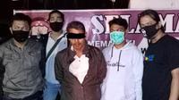 Pelaku (tengah) pencabulan terhadap anak kandungnya sendiri di Kota Padang. (Liputan6.com/ ist)
