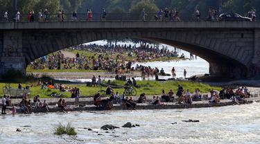Ribuan orang menikmati cuaca musim panas di tepi sungai 'Isar' di Munich, Jerman (19/7/2020). Di tengah pandemi COVID-19, ribuan orang menikmati cuaca musim panas di dekat sungai tersebut untuk berjemur serta mendinginkan tubuh. (AP Photo/Matthias Schrader)