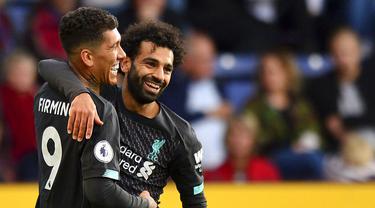 Striker Liverpool, Roberto Firmino, melakukan selebrasi bersama Mohamed Salah usai membobol gawang Burnley pada laga Premier League 2019 di Stadion Turf Moor, Sabtu (31/8). Liverpool menang 3-0 atas Burnley. (AP/Anthony Devlin)