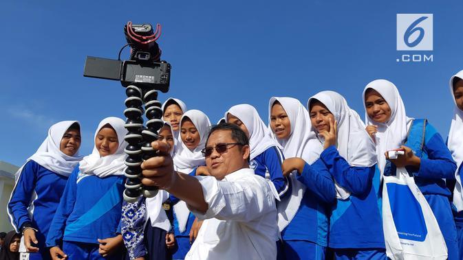 Menkominfo Rudiantara ngevlog dengan siswa di Taman Kota Morotai menggunakan WiFi publik yang dibangun BAKTI dan Lintasarta. (Liputan6.com/ Agustin Setyo W)