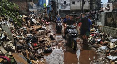 FOTO: Warga Bersihkan Sisa Banjir di Kebalen