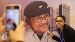 Pengunjung foto di depan poster Presiden ke-3 RI, Bacharuddin Jusuf Habibie saat pembukaan Habibie Festival di Museum Nasional, Jakarta, Kamis (11/8). Acara diadakan dalam rangka merayakan ulang tahun B.J Habibie ke-80. (Liputan6.com/Immanuel Antonius)
