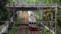 Rangkaian kereta commuter line saat melintas di dekat Stasiun Universitas Indonesia, Depok, Selasa (29/12/2015). Untuk mengakomodasi penumpang pada malam pergantian tahun, KRL Commuter Line akan beroperasi 24 jam. (Liputan6.com/Helmi Fithriansyah)