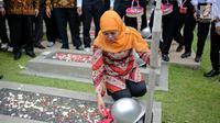 Menteri Sosial Khofifah Indar Parawansa menaburkan bunga di salah satu makam pahlawan di Taman Makam Pahlawan Kalibata, Jakarta, Senin (2/10). Mensos mengajak 50 santri penghafal Alquran untuk mendoakan para pahlawan nasional. (Liputan6.com/Faizal Fanani)