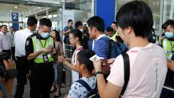 Petugas keamanan memeriksa informasi penerbangan para pelancong di gerbang pintu masuk utama bandara di Hong Kong, Rabu (14/8/2019). Bandara Hong Kong kembali membuka penerbangan keberangkatan pada Rabu pagi setelah sempat lumpuh selama dua hari terakhir akibat demonstrasi. (AP/Vincent Thian)