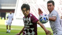 Pemain Shanghai SIPG, Mirahmetjan Muzepper, berebut bola dengan pemain Vissel Kobe, Daigo Nishi, pada laga Liga Champions Asia di Doha, Qatar, Senin (7/12/2/2020). Vissel Kobe menang dengan skor 2-0. (AP Photo/Hussein Sayed)