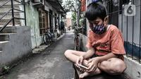Seorang anak mengenakan masker saat bermain di depan rumah di RW 004, Cipinang Melayu, Jakarta, Rabu (27/1/2021). Pemprov DKI Jakarta mencatat sebanyak 54 rukun warga (RW) menjadi zona merah Covid-19 per 21 Januari 2021. (merdeka.com/Iqbal S Nugroho)