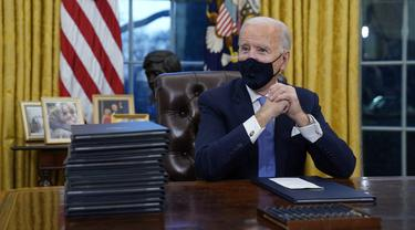 Presiden AS Joe Biden menunggu untuk menandatangani tindakan eksekutif pertamanya di Ruang Oval, Gedung Putih, Washington D.C pada Rabu (20/1/2021). (Photo credit: AP/Evan Vucci)