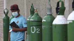 Seorang pria menunggu di dekat tabung oksigennya yang kosong dalam antrean di luar toko untuk mengisi ulang di tengah pandemi COVID-19 di kawasan kumuh Villa El Salvador di Lima, Peru, Kamis (21/1/2021). Toko dibatasi untuk mengisi ulang hanya 20 tabung oksigen dalam sehari. (AP Photo/Martin Mejia)