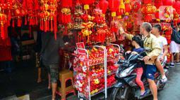 Pengendara motor melihat pernak-pernik Imlek yang dijual di kawasan Glodok, Jakarta, Senin (13/1/2020). Menyambut tahun baru Imlek pada 25 Januari mendatang, penjualan pernak-pernik imlek dijual dengan harga Rp 5ribu hingga jutaan rupiah per buah tergantung jenis. (merdeka.com/Arie Basuki)