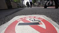 """Peringatan larangan merokok di Tokyo dalam tulisan Jepang: """"Dilarang Merokok di Jalanan, Denda 2.000 yen"""". (AP Photo/Shizuo Kambayashi)"""