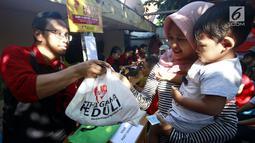Panitia AGP membagikan paket sembako kepada warga kurang mampu di Rawa Badak Selatan, Jakarta Utara, Kamis (13/6). Kegiatan ini digelar untuk meringankan beban keuangan masyarakat kurang mampu yang tidak melakukan mudik lebaran.  (Liputan6.com/HO/Rizki)