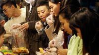 Pembeli mencicipi kue kering untuk perayaan tahun Baru Imlek di pasar Dihua Street, Taipei di Taiwan, Selasa (22/1/2020). Pembeli mulai berburu makanan lezat, kue kering, barang-barang murah lainnya di pasar menjelang Imlek yang akan berlangsung pada 25 Januari mendatang. (AP Photo/Chiang Ying-ying)