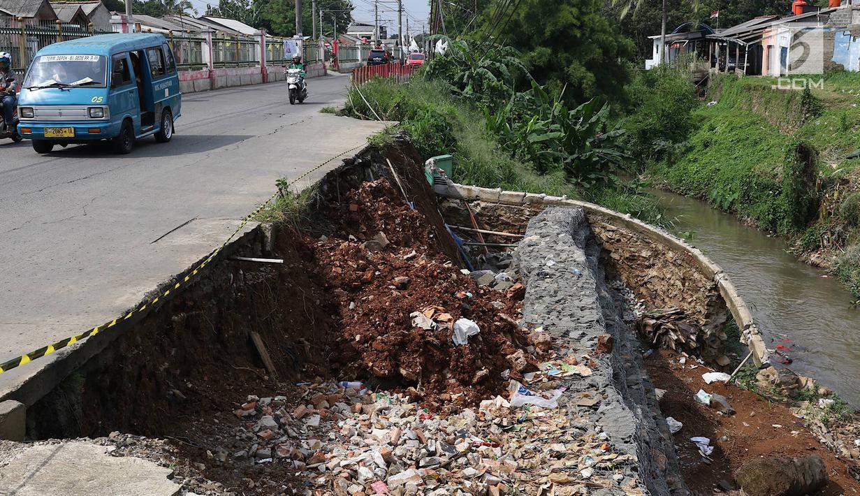 Kendaraan melintas di samping Jalan Raya Citayam yang amblas di kawasan Cipayung, Depok, Jawa Barat, Rabu (27/2). Kondisi tepi jalan yang tidak kunjung diperbaiki membahayakan pengguna jalan terutama saat malam hari. (Liputan6.com/Immanuel Antonius)