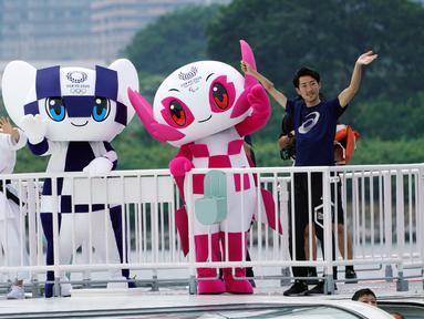 Maskot Olimpiade dan Paralimpik Tokyo 2020, Miraitowa (kiri) dan Someity (kanan) melambaikan tangan saat menaiki perahu di Rainbow Bridge, Tokyo, Jepang, Minggu (22/7). Miraitowa dan Someity resmi diperkenalkan kepada publik. (AP Photo/Eugene Hoshiko)