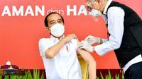 Presiden Joko Widodo atau Jokowi (kiri) disuntik vaksin COVID-19 di Istana Merdeka, Jakarta, Rabu (13/1/2021). Vaksinator menyuntikkan vaksin di lengan kiri Presiden Jokowi sekitar pukul 09.42 WIB. (Biro Pers Sekretariat Presiden/Laily Rachev)