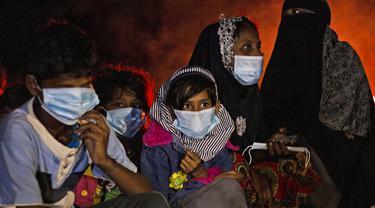Perempuan dan anak-anak etnis Rohingya duduk dekat api unggun setelah kapal mereka terdampar di Pulau Idaman, Aceh Timur, Aceh, Jumat (4/6/2021). Kapal yang mengangkut 81 pengungsi Rohingya terdampar di Pulau Idaman. (AP Photo/Zik Maulana)