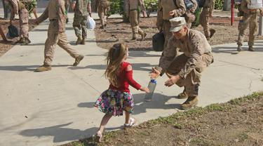 Seorang Angkatan Laut AS menyambut anaknya saat tiba di Camp Pendleton di Oceanside, California, AS, Kamis (11/5). (AFP/ Sandy Huffaker)