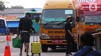 Sebuah bus sekolah disiagakan di Terminal bus Kalideres, Jakarta Barat, Senin (17/5/2021). Bus sekolah tersebut untuk membawa penumpang yang positif Covid-19 menuju Puskesmas Kalideres guna menjalani tes polymerase chain reaction (PCR). (Liputan6.com/Angga Yuniar)